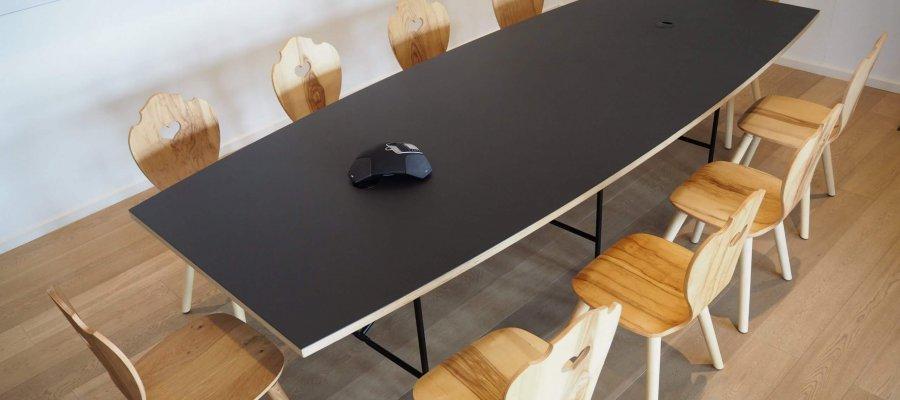 Moderner Meetingraum schwarzer Tisch mit modernen Holzstühlen im Alpenstyle