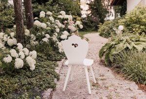 weißer SÜSSHOLZ Herzerlstuhl neben weißen Hortensien