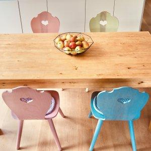 bunt geölte Herzerlstühle am Küchentisch aus Eiche mit einer Schüssel Äpfel