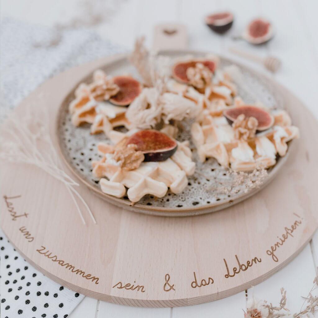 Teller mit Waffeln und Feigen auf Holzbrett mit schöner Gravur